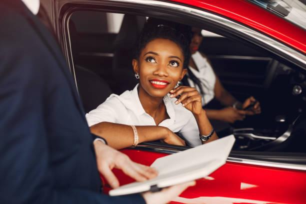 Two stylish black women in a car salon stock photo