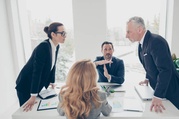 two stylish business persons in suits having disagreement, war, conflict, standing near desktop in front of each other, face to face with disrespect expression, partner showing stop sign with hands - guerra imagens e fotografias de stock