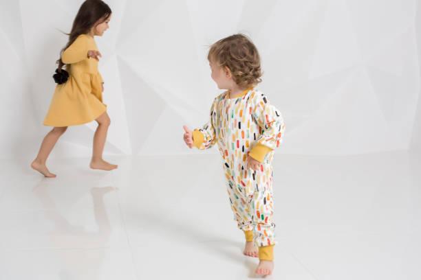 zwei stilvolle mädchen laufen nacheinander auf weiße wand hintergrund - festliche babymode junge stock-fotos und bilder