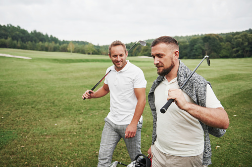 Two stylish men holding bags with clubs and walking on golf course