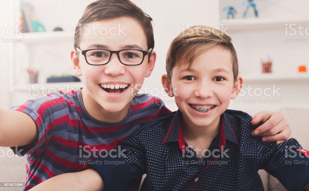 Two stylish smiling teens taking selfie stock photo
