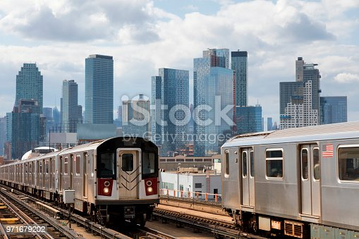 Two subway trains speeding on elevated track in Queens, New York. Financial and residential buildings are seen in background, USA