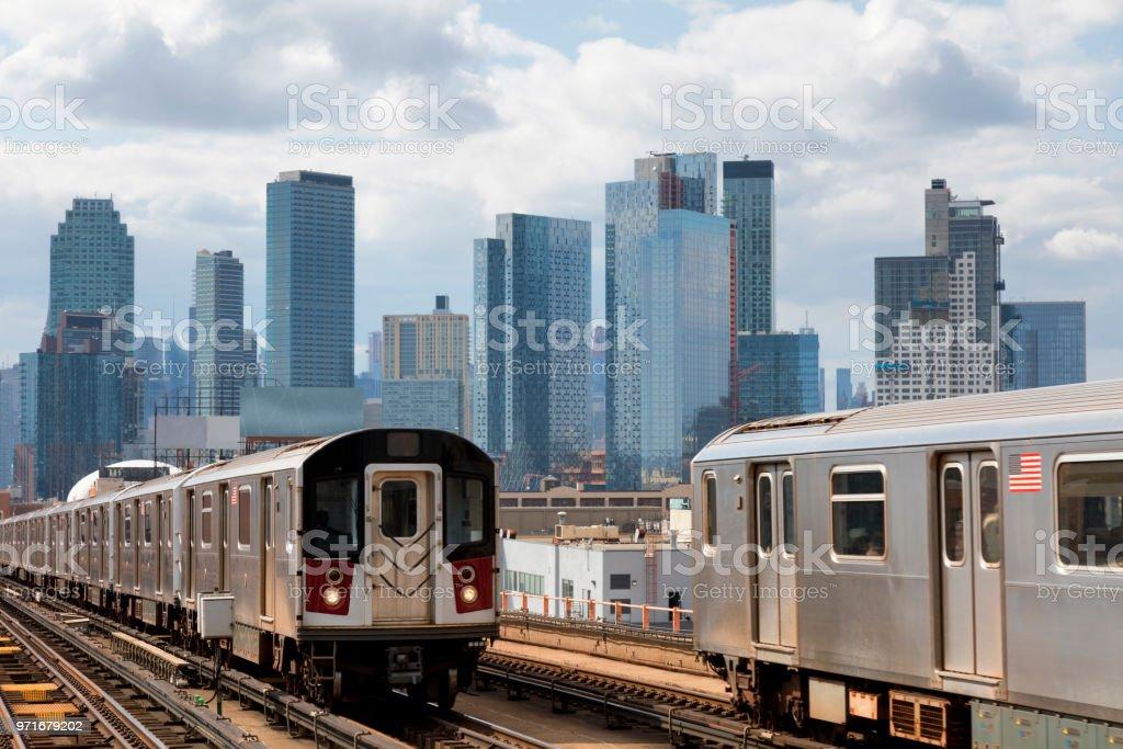 Zwei U-Bahn-Züge, die Beschleunigung auf erhöhten verfolgen in Queens, New York – Foto