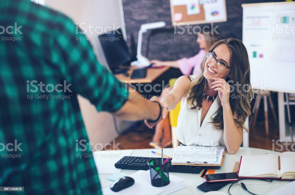 Two successful business partner shaking hands in the office stock photo
