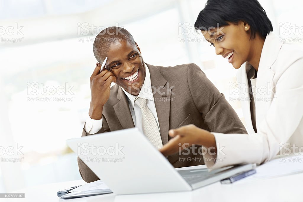 Two successful business people working on a laptop at office royalty-free stock photo
