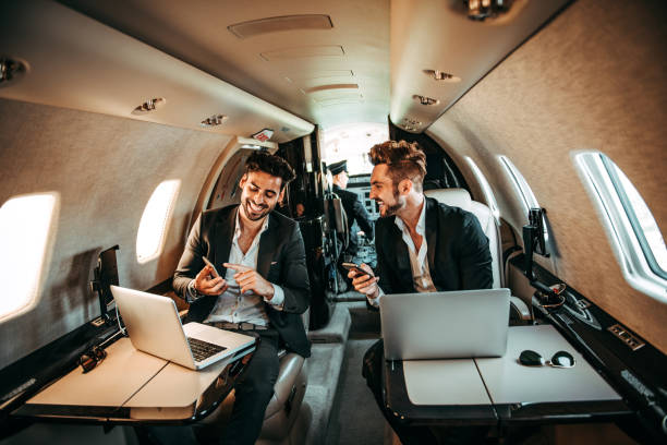 Two successful corporate managers using mobile phones while working on laptops together are flying on a private jet Two successful corporate managers using mobile phones while working on laptops together are flying on a private airplane. Digital tablet, sunglasses and a mobile phone are on their respective tables. status symbol stock pictures, royalty-free photos & images
