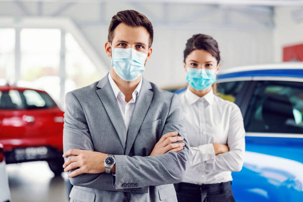 Two successful, proud car sellers standing with arms crossed in car salon and having face masks on faces. stock photo