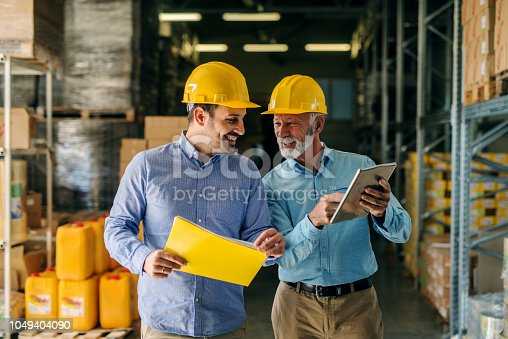 Two successful smiling business man walking through big warehouse with helmets on their heads. Older man is holding digital tablet and shoving younger one some documents.