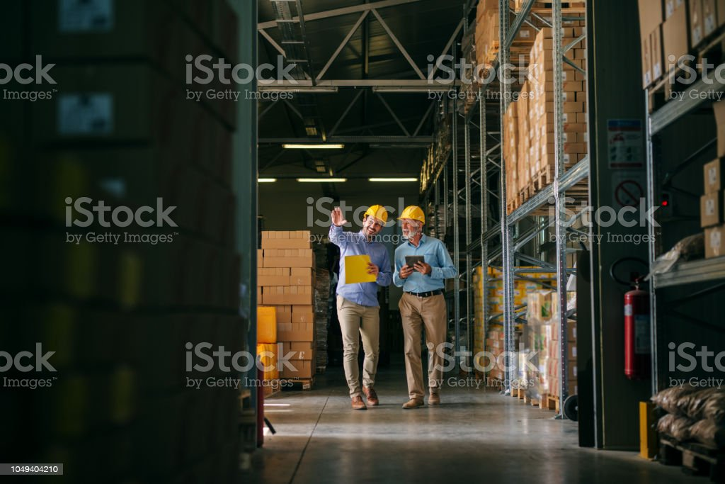 Two successful smiling business man walking through big warehouse with helmets on their heads.Younger man is shoving older one shelf's full of products ready to be delivered. Happy investors. stock photo