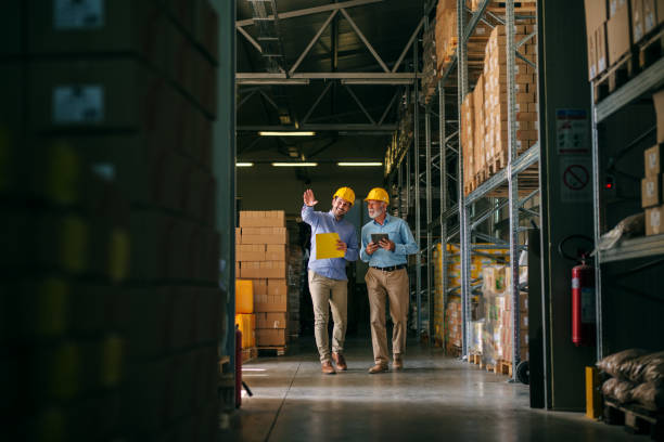 two successful smiling business man walking through big warehouse with helmets on their heads.younger man is shoving older one shelf's full of products ready to be delivered. happy investors. - ripostiglio luogo di lavoro foto e immagini stock