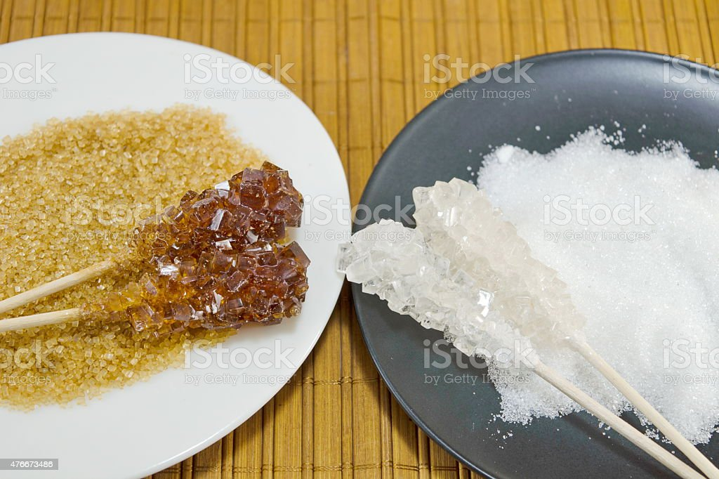 Two sugar sticks containg white and brown sugar stock photo