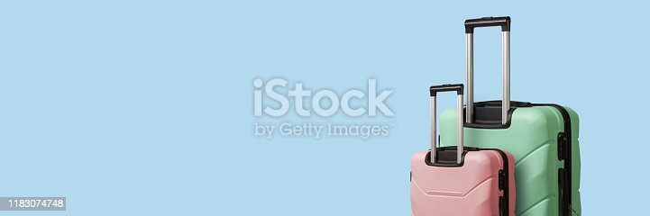 Two Suitcases on wheels on a blue background. Concept of travel, a vacation trip, a visit to relatives. Pink and Green color. Banner.
