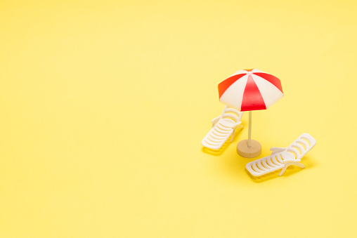 Two sun loungers and a red umbrella on a yellow background. Copy space.