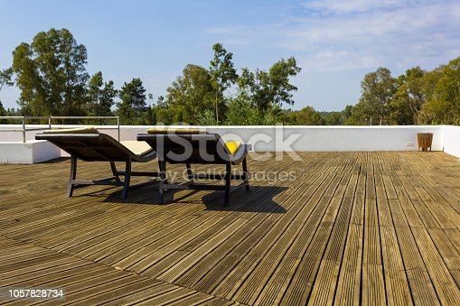 istock Two sunbeds in the sun on the wooden dais 1057828734
