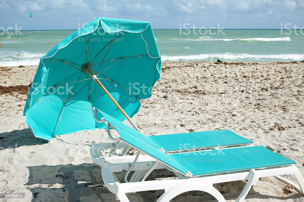Two Sunbeds With Turquoise Cushions And Felled Turquoise Umbrella stock photo