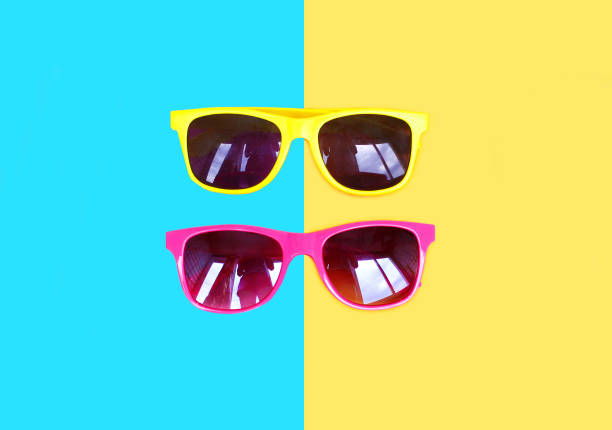 Two sunglasses yellow pink over a colorful background – Foto