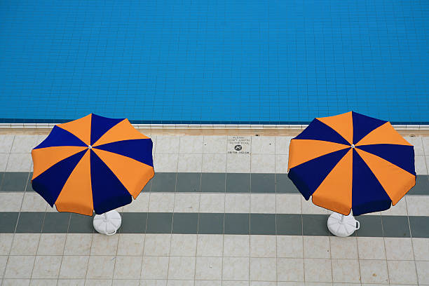 two sunshades along the pool - decagon stock pictures, royalty-free photos & images