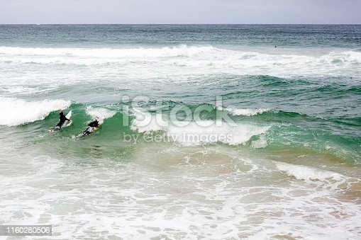 Two surfers and braking ocean waves, background with copy space, full frame horizontal composition