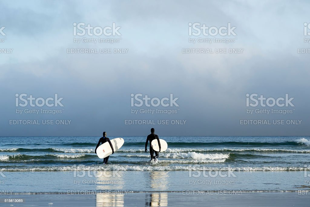 Two surfers in wetsuits walking into the Pacific Ocean stock photo