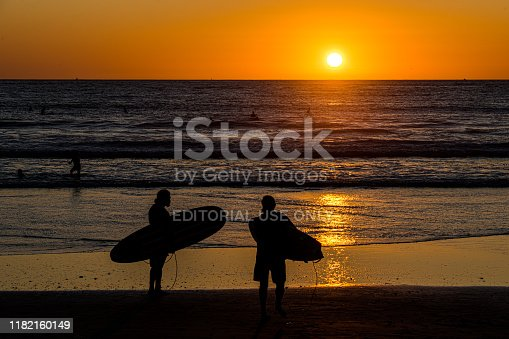Two surfers wading into the surf at sunset near Ocean Beach, California.