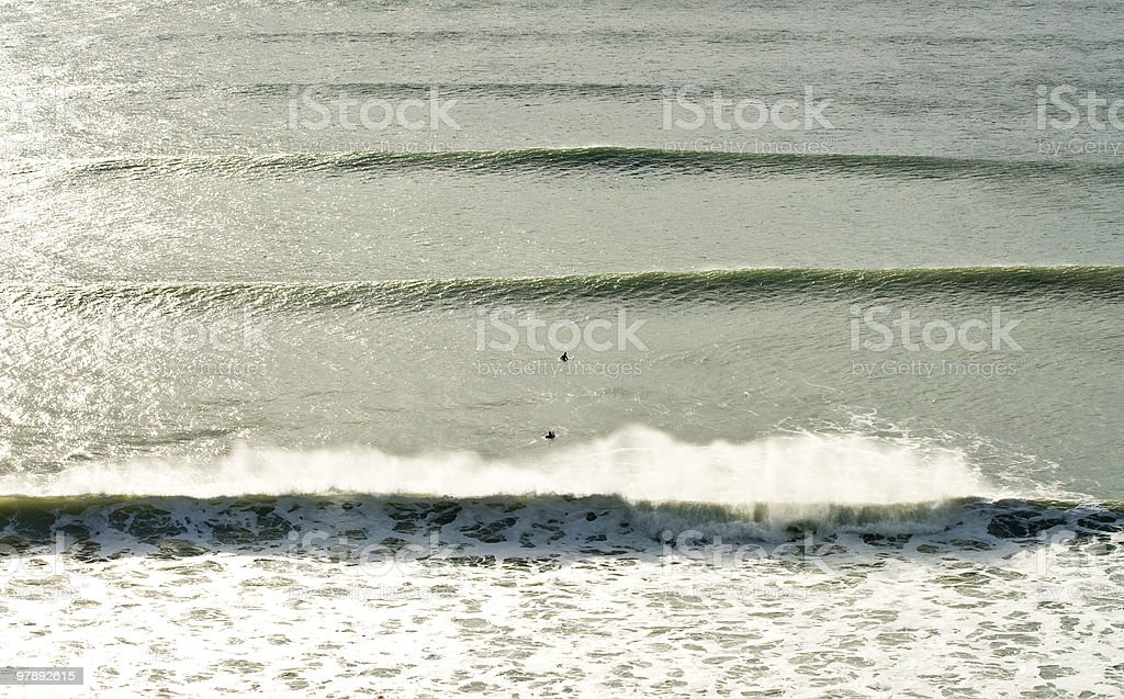 two surfers sitting between waves royalty-free stock photo