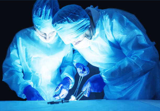 two surgeons, a man and a woman, perform surgery to remove prostate adenoma and varicocele, fibroadenoma - ernia foto e immagini stock