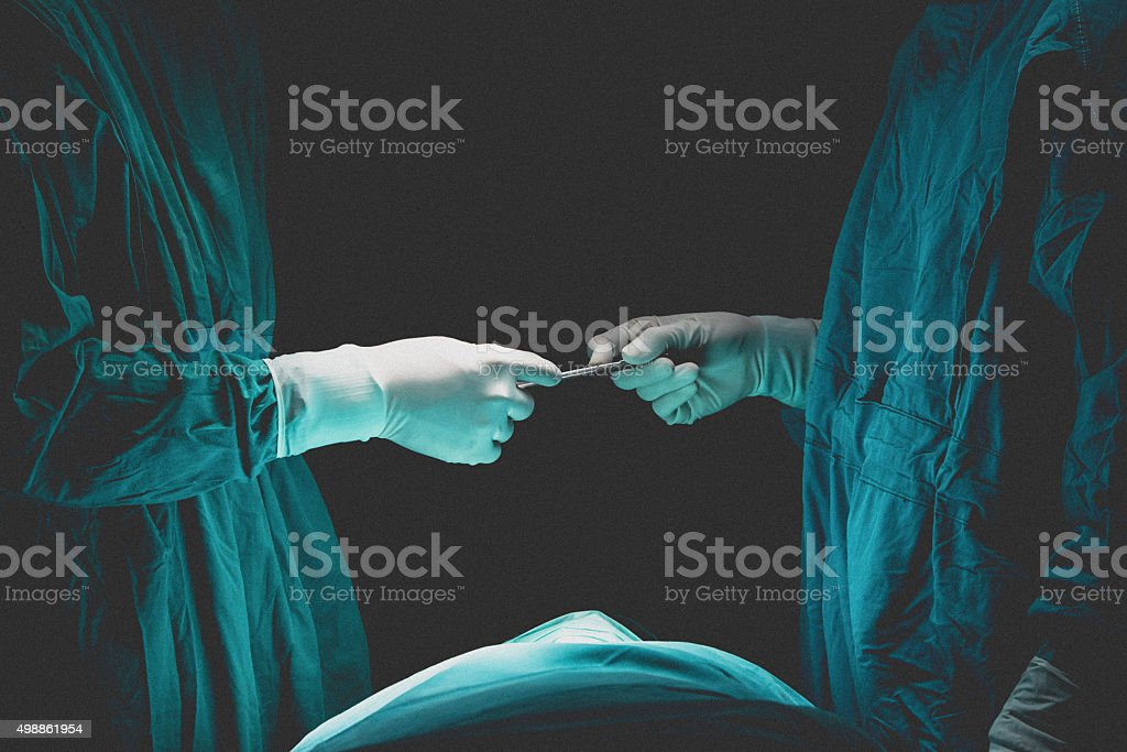 Two surgeons working and passing surgical equipment stock photo
