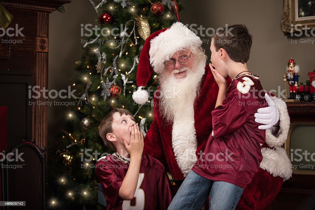 Two Surprised Boys Sit on Santa's Lap in Living Room stock photo