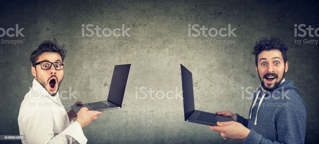 Two surprised funny men with new laptops stock photo