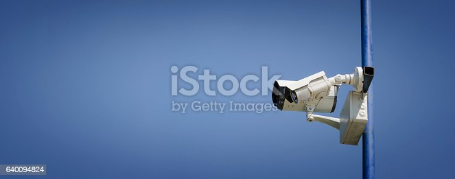 istock Two surveillance cameras on a pole with blue sky background 640094824