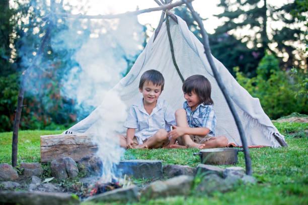 zwei süße kinder, junge brüder, camping außerhalb der sommerzeit am sonnenuntergang, essen kartoffeln - weidentipi stock-fotos und bilder