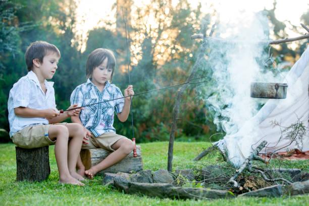 zwei süße kinder, junge brüder, camping außerhalb sommer auf sonnenuntergang - weidentipi stock-fotos und bilder