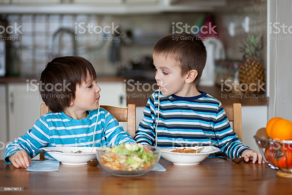 Two sweet children, boy brothers, having for lunch spaghetti at stock photo