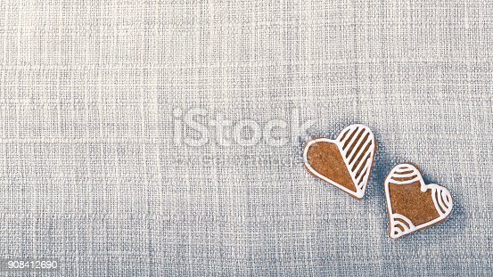 Background from fabric texture and hand-decorated pastries in heart shape with copy space