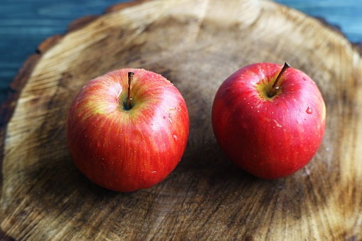 Two sweet ripe juicy red apples on chopped wood close up