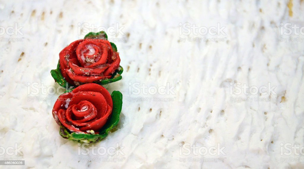 Two sweet sugar roses on a wedding cake stock photo