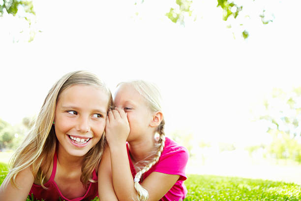 two sweet young girls sharing a secret together - tween models stock photos and pictures