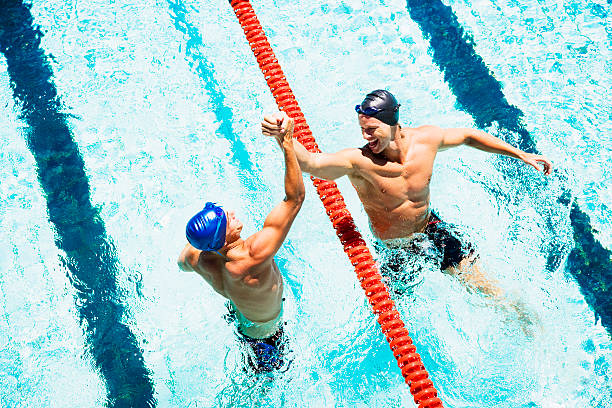 Two swimmers in a pool joining hands stock photo