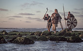 Two sword wielding bloody medieval warriors together on a cold seashore