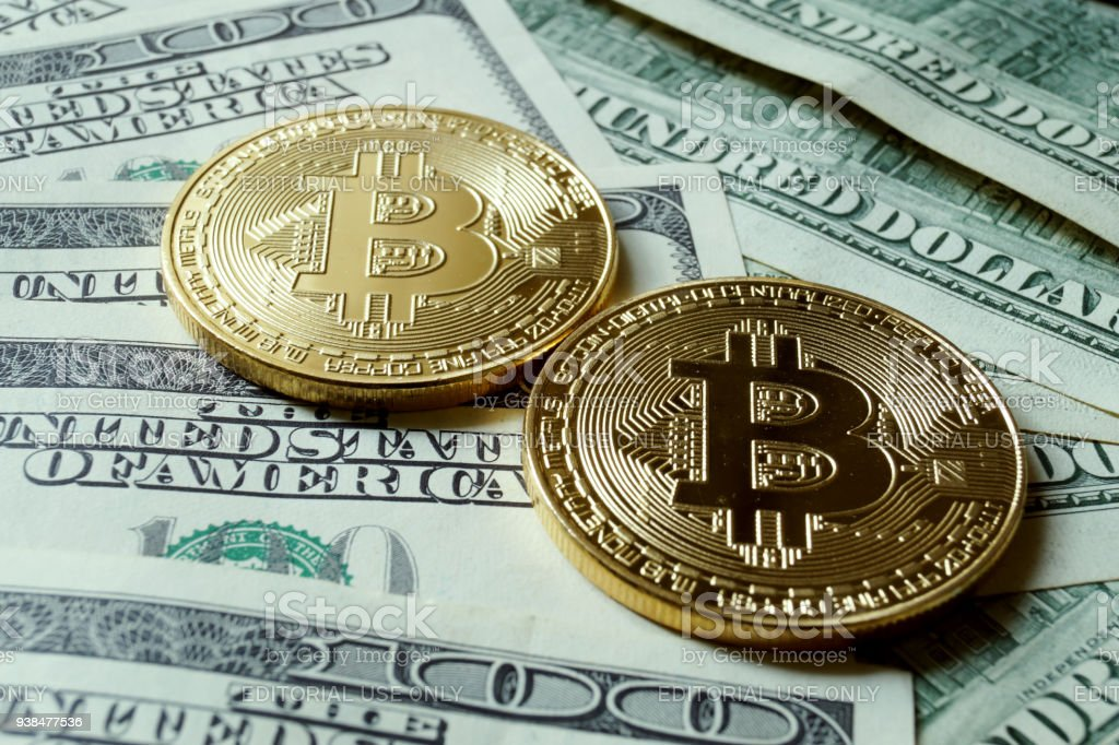 Two symbolic coins of bitcoin on banknotes of one hundred dollars. stock photo