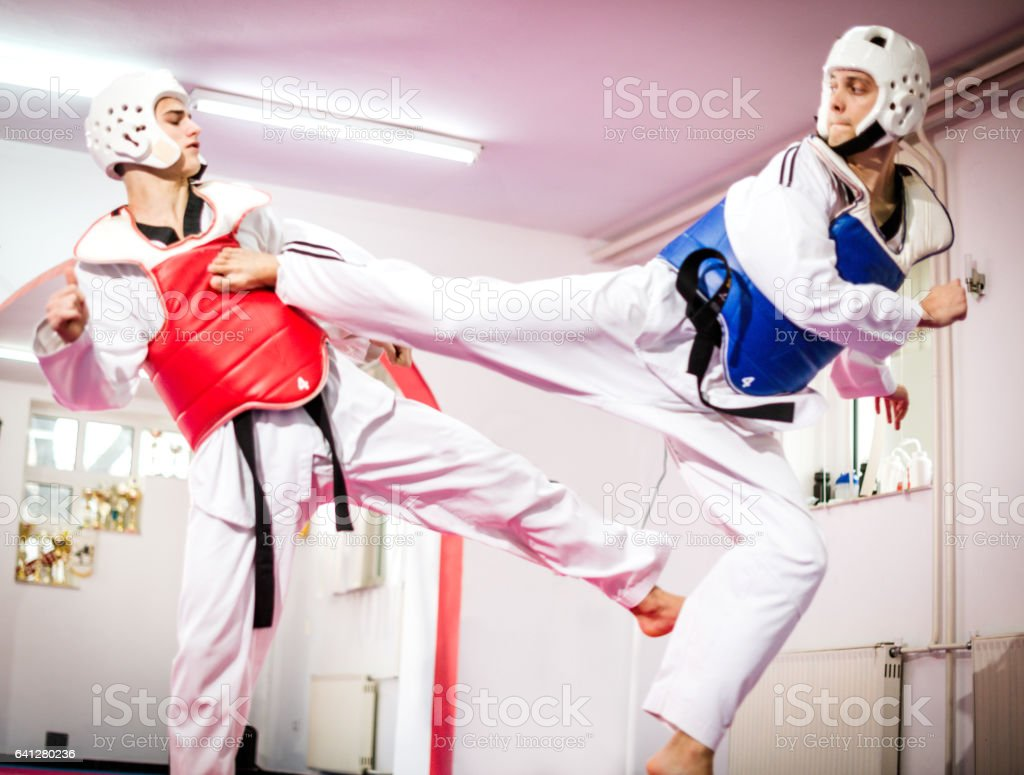 Two taekwondo fighters compete and practice high kicks with protective equipment stock photo