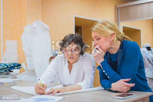 istock Two tailors discussing pattern of new dress 979237212