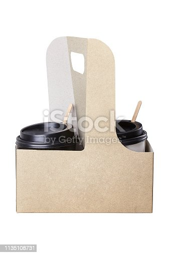 Two take-out coffees with  with brown caps in paper cup holder. Isolated on a white. Two paper coffee cups. Vertical. Two cups with brown safety cardboard collars.  Take away box for two cups
