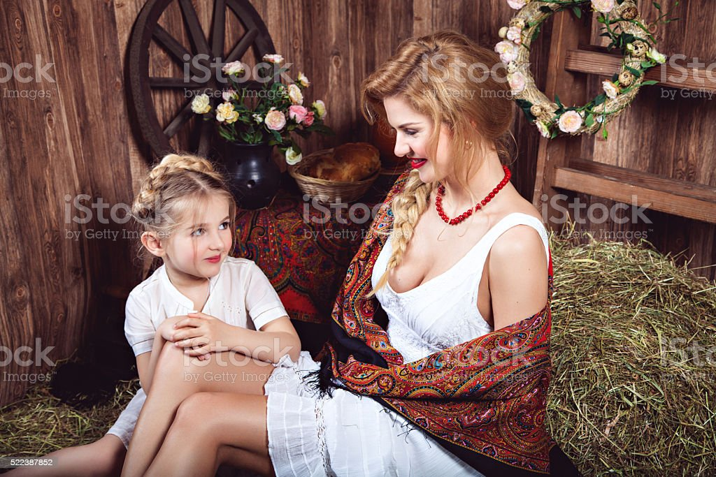 Two talking countrywomen sitting on the haystack stock photo