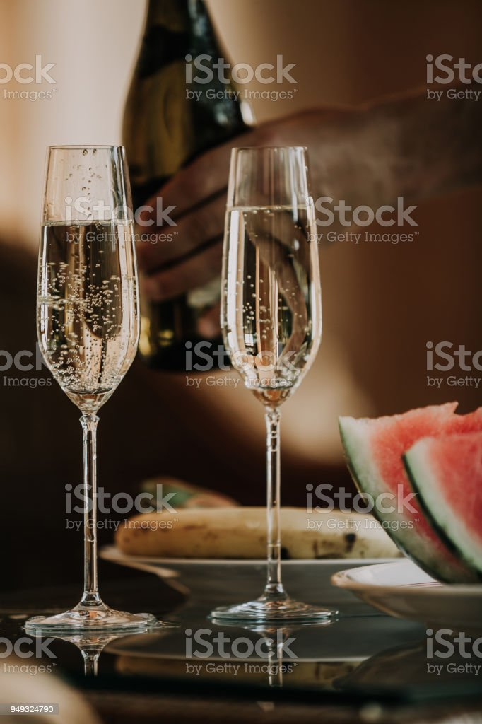 Two beautiful elegant glasses with champagne are on the table. At the...