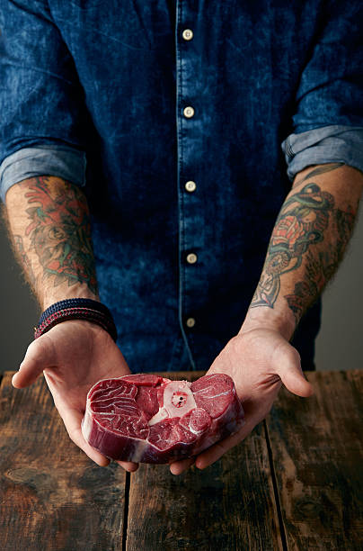 Two tattooed hands holds meat steak gently stock photo