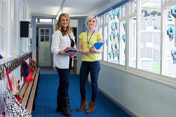 two teachers in school corridor - erzieherin stock-fotos und bilder