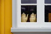 Varmahlid, Iceland - August 2010: Two teapots decorating a white window in a yellow facade house at Glaumbaer Museum