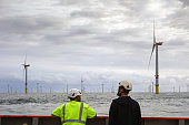 Two Technician standing on transfer vessel deck and in the morning and looking on offshore wind farm and offshore platform around in German north sea