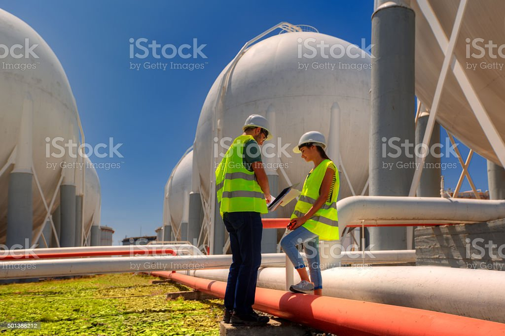 Two technicians in the refinery area is inspected stock photo